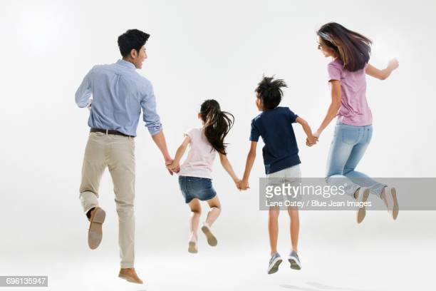 Cheerful young family jumping