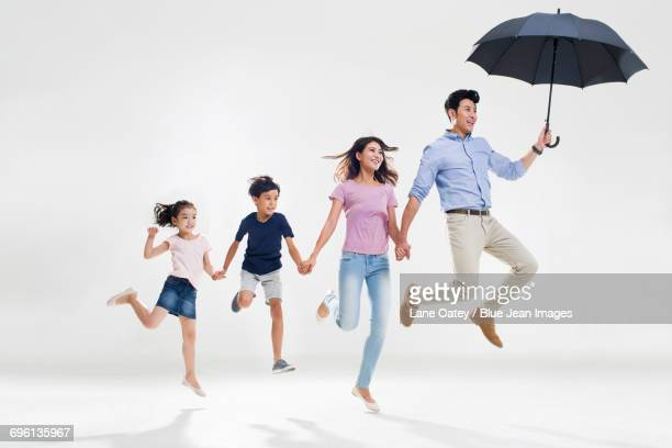 Cheerful young family jumping with an umbrella