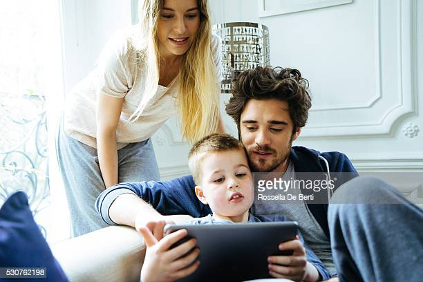 Cheerful Young Family Looking At Digital Tablet Together