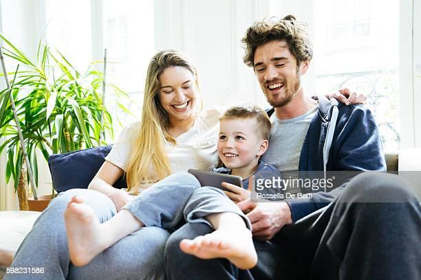 Gai jeune famille regardant tablette numérique ensemble
