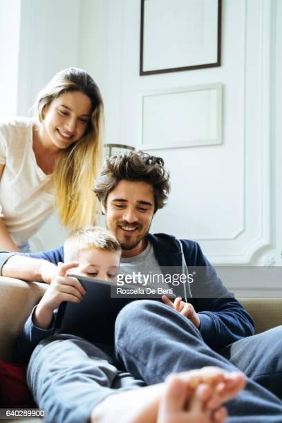 陽気な若い家族を見ているデジタルタブレット一緒