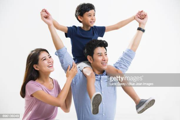 cheerful young family - carrying a person on shoulders stock photos and pictures