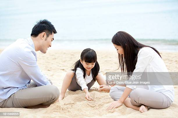 Cheerful young family playing with sand on the beach of Repulse Bay, Hong Kong