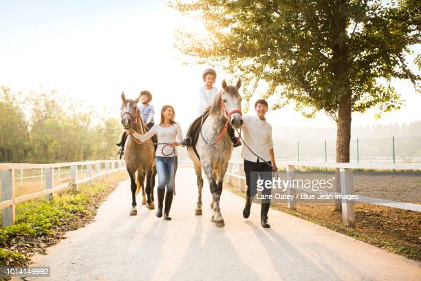 Cheerful young family riding horses