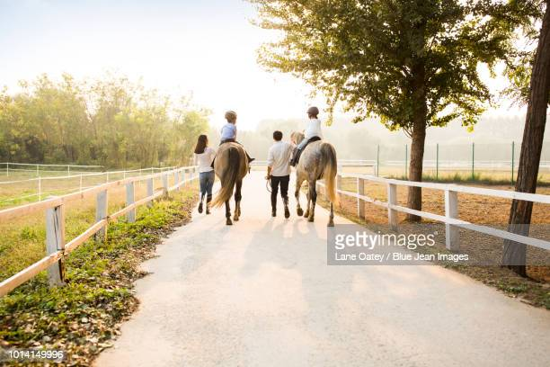 cheerful young family riding horses - wide shot stock pictures, royalty-free photos & images