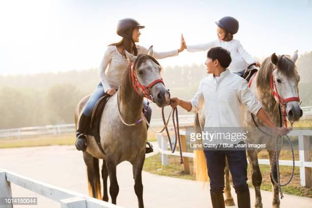cheerful young family riding horses - paard paardachtigen stockfoto's en -beelden