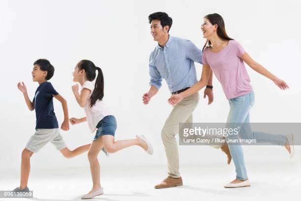 cheerful young family running - 近く ストックフォトと画像