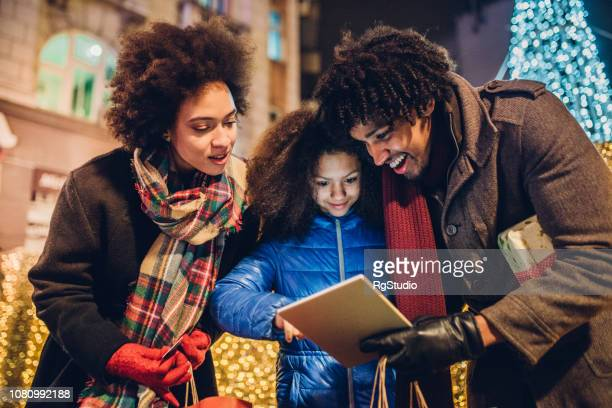 Cheerful young family shopping for Christmas presents online