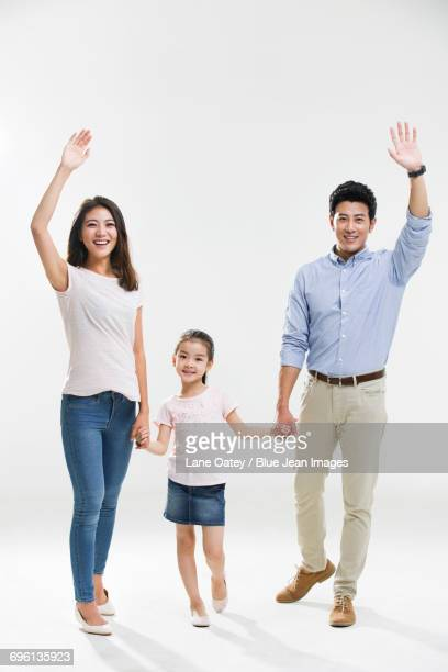 Cheerful young family waving
