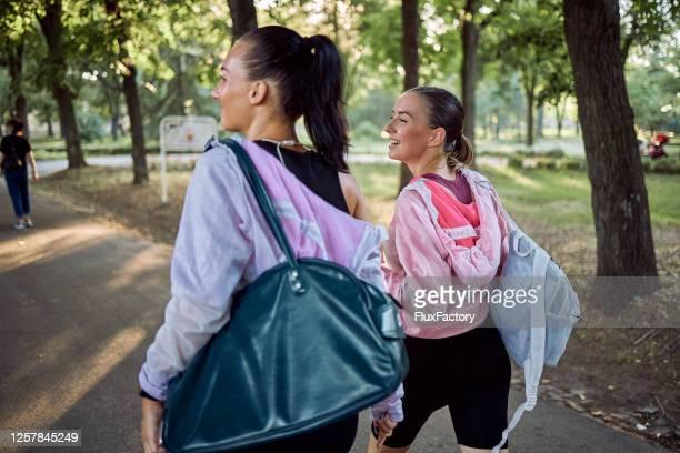 ジムバッグを持ったトレーニングから戻ってくる陽気な若い女性アスリート - スポーツバッグ ストックフォトと画像