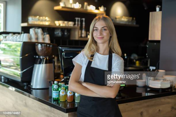 cheerful young female coffee shop barista - franchising stock pictures, royalty-free photos & images