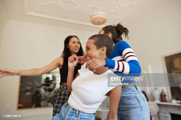 cheerful young female friends enjoying in bedroom - female friendship stock pictures, royalty-free photos & images