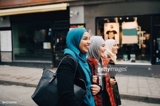 Cheerful young female friends walking with arms in arms on street in city