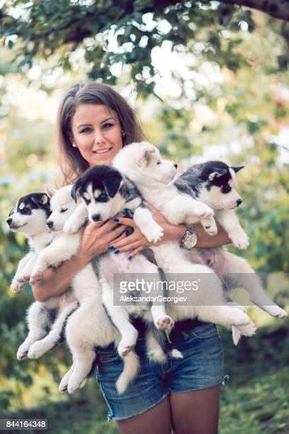 Fröhlich junge weibliche Holding fünf wunderschönen Husky Baby-Klößchen