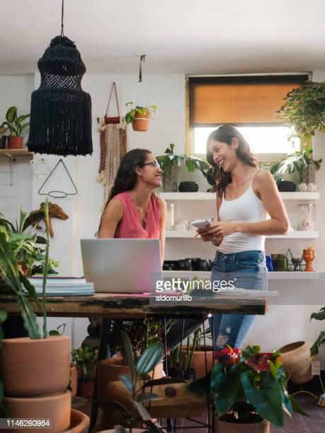 vrolijke jonge vrouwelijke storeowners glimlachend op elkaar - nosotroscollection stockfoto's en -beelden