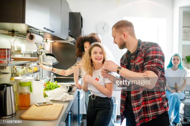cheerful young flatmates with friends in the kitchen - roommate stock pictures, royalty-free photos & images