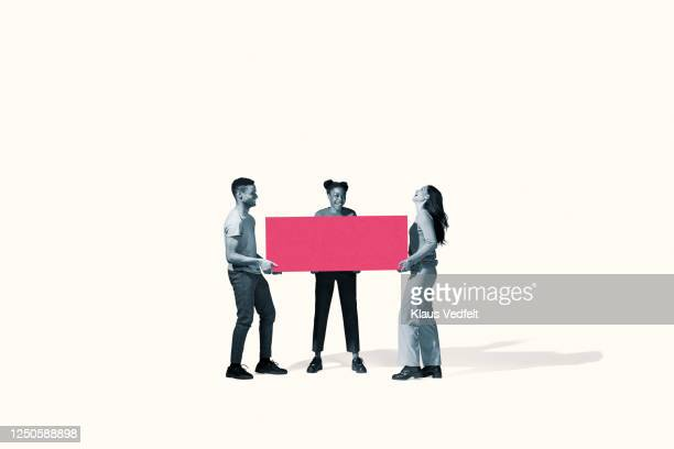 cheerful young friends carrying large pink block - three people fotografías e imágenes de stock