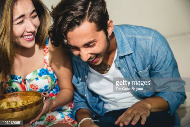 cheerful young friends laughing while sitting on sofa during party - hysteria stock pictures, royalty-free photos & images