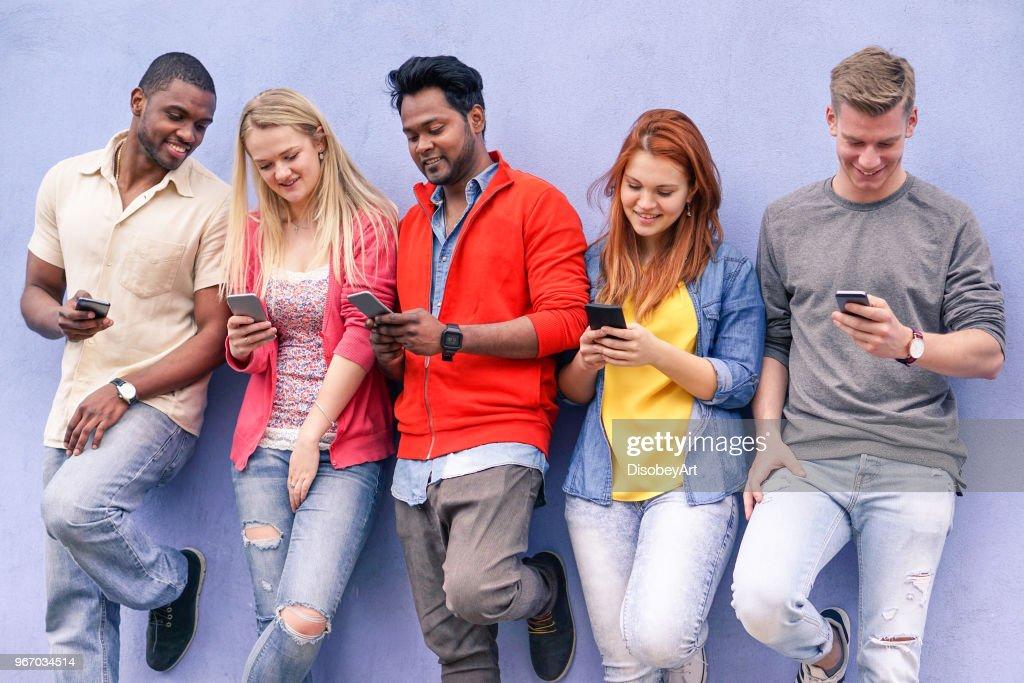 Fröhliche Junge Freunde suchen Smartphone - Mischlinge Menschen mit Mobiltelefon mit blauen Wand Hintergrund - freundschaft fun-Konzept mit Trend-Technik-Interaktion - Soft-Fokus auf Jungs in Mitte : Stock-Foto
