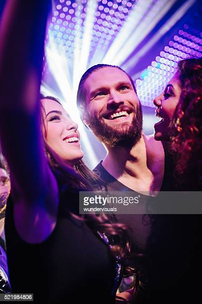 Cheerful young friends taking selfie at the club