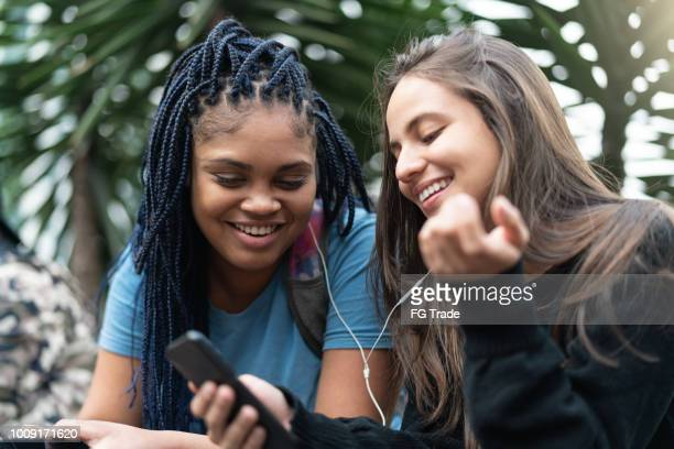 cheerful young friends using phone - baby mobile stock photos and pictures