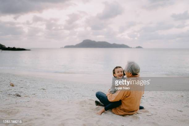 cheerful young girl cuddling her grandfather on beach at sunset - tropical climate stock pictures, royalty-free photos & images