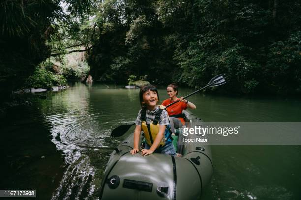 cheerful young girl having fun on kayak with mother in rainforest, japan - 埼玉県 ストックフォトと画像