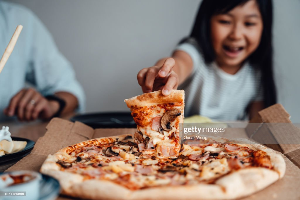 Cheerful Young Girl Holding A Slice Of Pizza : Stock Photo