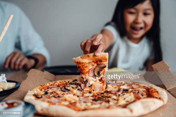 cheerful young girl holding a slice of pizza - indulgence stock pictures, royalty-free photos & images