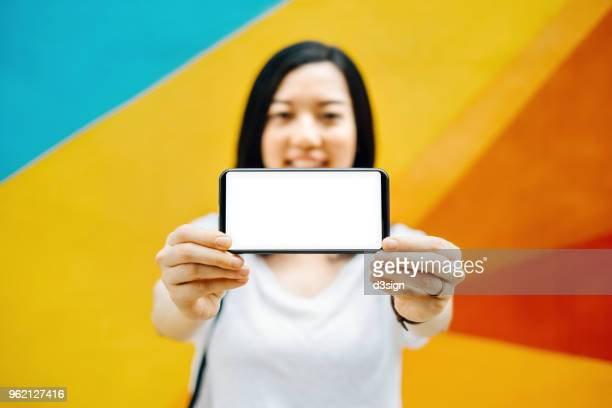 cheerful young girl holding smartphone on hand with a blank screen against colourful background - tonen stockfoto's en -beelden
