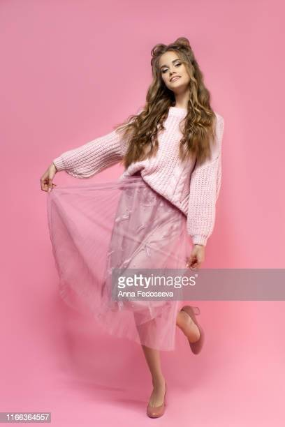 cheerful young girl in a pink skirt, knitted sweater, shoes with heels on a pink background with an odango hair and curly long hair. pink total look. fashion clothes. - pink skirt stock pictures, royalty-free photos & images