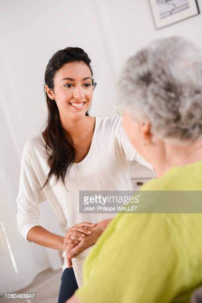 cheerful young girl taking care of elderly senior woman at home - over 80 stock pictures, royalty-free photos & images