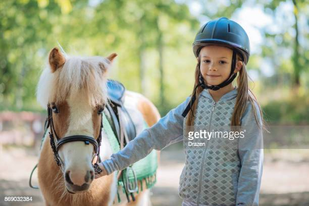 cheerful young girl with her pony horse - riding hat stock pictures, royalty-free photos & images