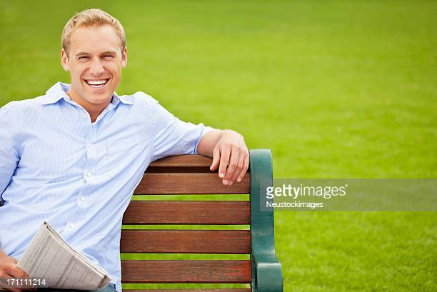 Cheerful Young Guy Sitting On a Park Bench