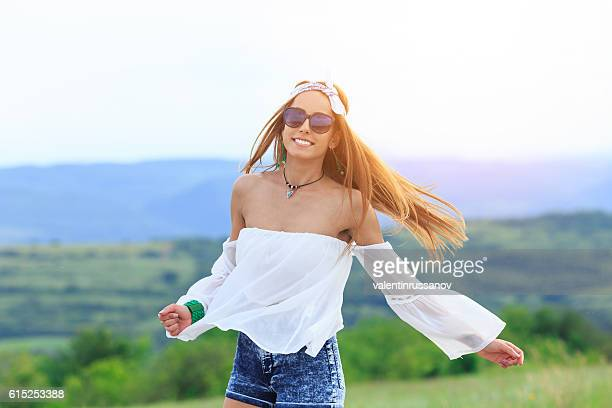 Cheerful young hippie woman dancing on country road