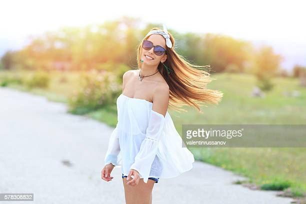 Cheerful young hippie woman on the road