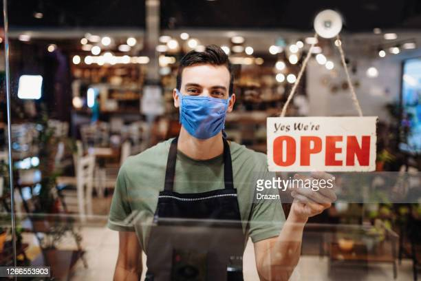 cheerful young latino waiter with face mask holding open sign in cafe - reopening stock pictures, royalty-free photos & images