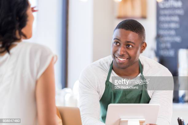 Cheerful young male coffee shop barista takes customer's order