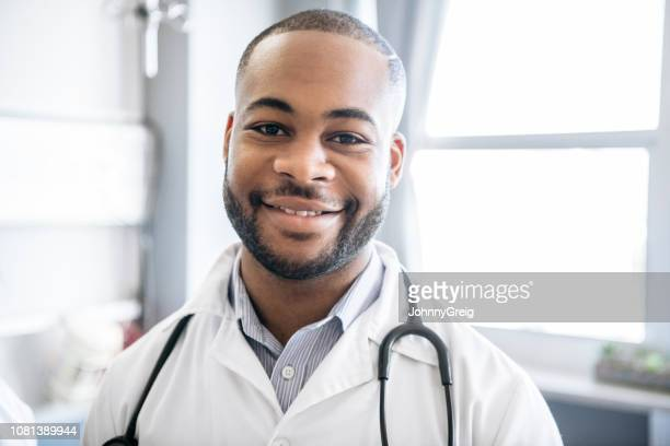 cheerful young male doctor in white coat smiling - junior doctor stock pictures, royalty-free photos & images