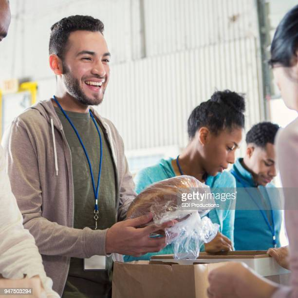 Cheerful young male food bank volunteer passes out bread
