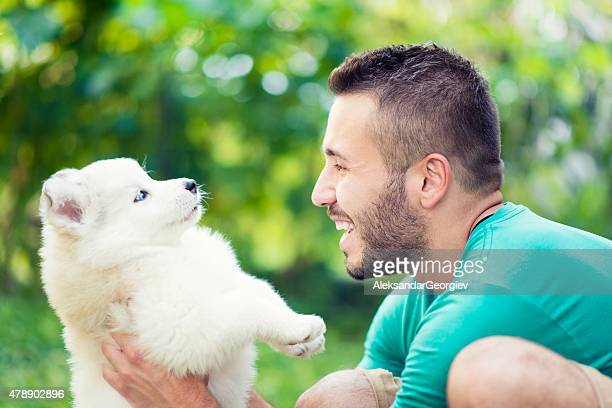 Cheerful Young Male Holding his Lovely Husky Baby Puppy