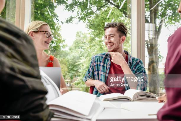 Cheerful young male student laughing with friends, text books on table