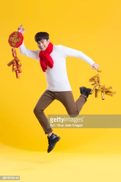 Cheerful young man celebrating Chinese new year with petards
