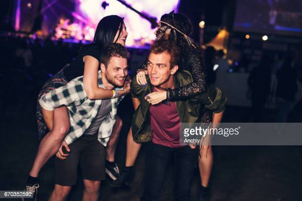 Cheerful young man giving a piggyback rides to their girlfriends at the spring music festival