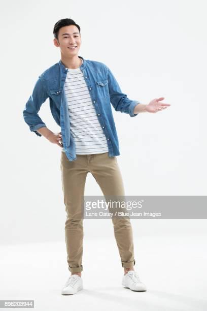 cheerful young man greeting - braccia tese foto e immagini stock