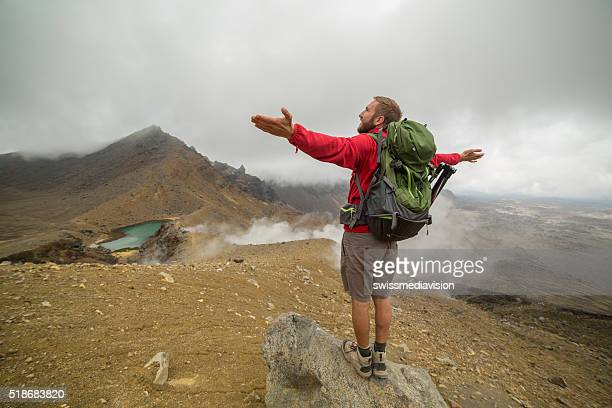 Cheerful young man hiking on Tongariro Alpine Crossing stretches arms