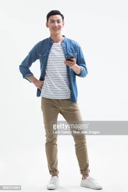 cheerful young man holding a smart phone - カジュアルウェア ストックフォトと画像
