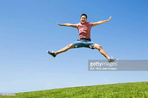 Cheerful young man jumping on grass