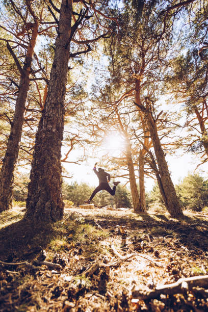 Cheerful young man jumping on land in forest