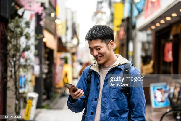 cheerful young man looking at smartphone in street - handsome chinese men stock pictures, royalty-free photos & images